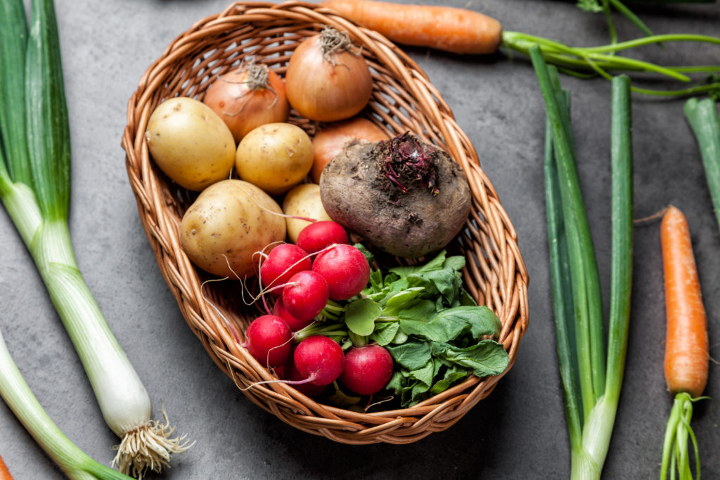 Fresh and healthy organic root vegetables on a rustic background