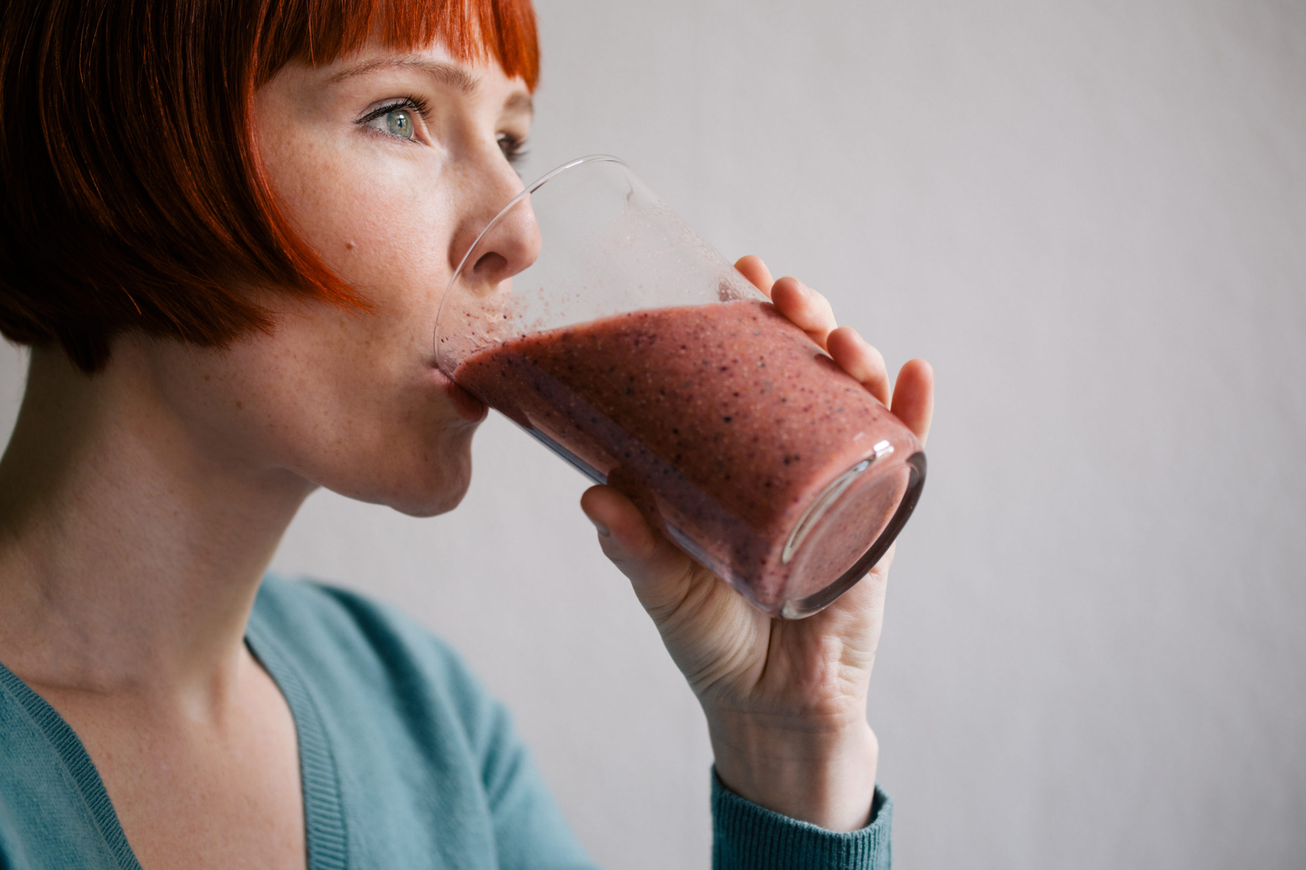 red-haired-woman-drinking-smoothie-QH259ZS