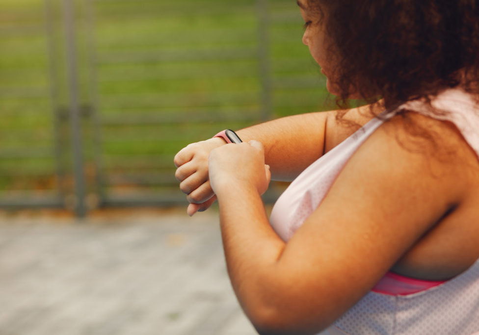 Young tired plus size woman. Girl training in a park. Woman with fithess tracker.
